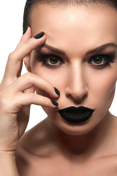 Beautiful female model with black caviar on his lips and nails